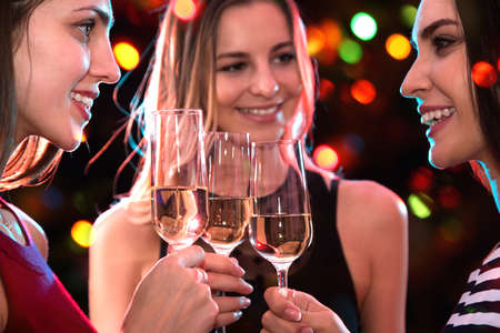 Photo pour Beautifully dressed young girls with glasses of wine at a Christmas party - image libre de droit
