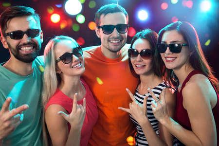 Photo pour Group of happy friends posing in the night club - image libre de droit