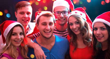 Photo pour Group of happy friends posing in Santa's hats at a Christmas party - image libre de droit