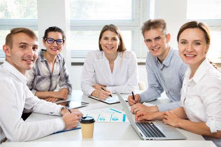 Foto de Young business people in office smiling looking at camera - Imagen libre de derechos