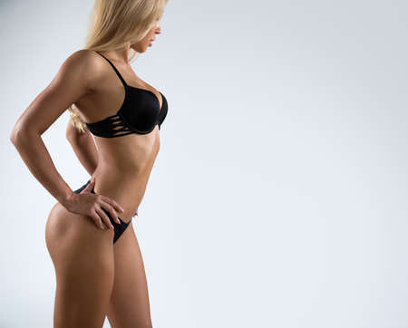 Photo pour Beautiful woman with a perfect body in a lingerie on a gray background - image libre de droit
