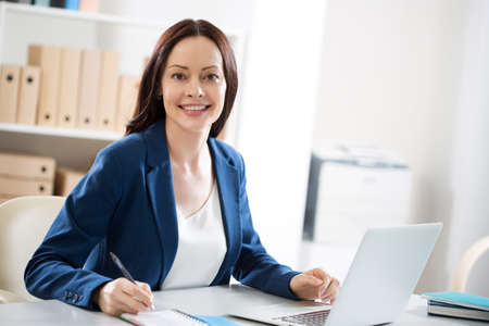Photo for Portrait of a pretty business woman at workplace in office - Royalty Free Image