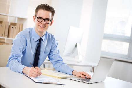 Photo pour Portrait of happy young businessman working with laptop at office - image libre de droit