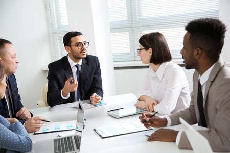 Foto de Multy-ethnic group of business people working at the office desk - Imagen libre de derechos