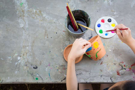 Foto de Asian girl studying and learning the art,the kid using paintbrush to painting water color on the potted plant made of pottery,concept art learning and education,hobby and activity - Imagen libre de derechos
