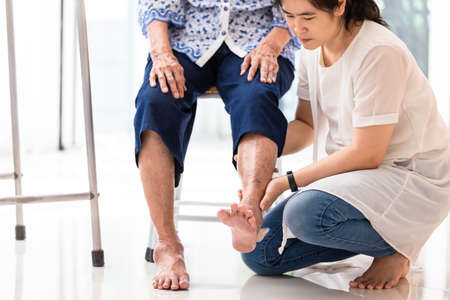 Foto de Asian young woman checking knee of elderly woman at home,senior woman receiving massage by female physic therapist of her leg due to injury - Imagen libre de derechos