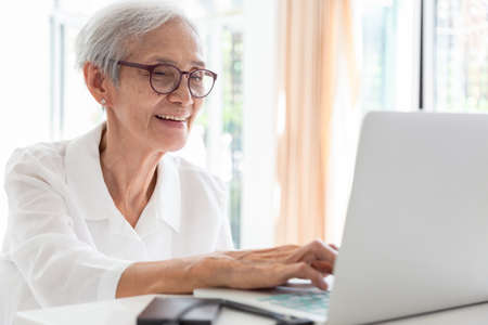 Happy asian senior woman working,surfing the internet with laptop computer at table in home,smiling elderly people in glasses with white hair sits in front of the computer and serf web-sites, technology and education concept