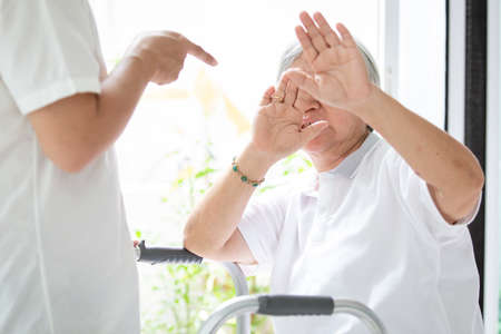 Photo pour Asian elderly woman were physically abused,attacking in house,angry man raised punishment fist,stop physical abuse senior people,caregiver,family stop violence and aggression concept - image libre de droit