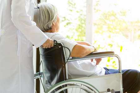 Foto de Caring doctor or nurse supporting disabled,alzheimer senior asian woman on wheelchair,female caregiver walking,elderly patient with depressive symptoms need close care,healthcare,depression concept - Imagen libre de derechos