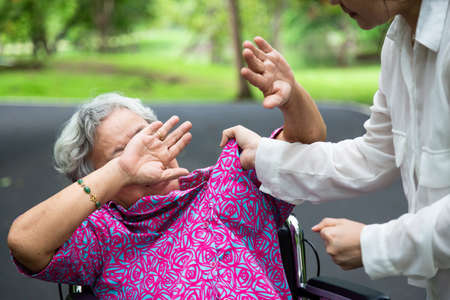 Photo pour Asian elderly woman were physically abused in wheelchair,attacking in outdoor park,angry young woman raised punishment fist,stop physical abuse senior people,caregiver,family stop violence and aggression concept - image libre de droit