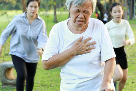 Photo pour Asian elderly woman having difficulty breathing suffer from heart attack,heart problem while walking exercise at park, daughter and granddaughter are running to help,senior mother feeling chest pain - image libre de droit