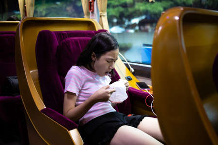 Photo pour Unhappy asian child girl about to throw up,puking,motion sickness symptoms, holding sick bag,sad female teenage vomiting in a bus suffers from motion sickness,feels dizziness and nausea from carsick - image libre de droit