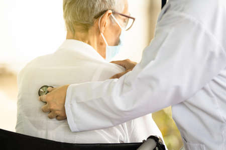 Photo pour Close up of a female doctor's hand using stethoscope listening to heartbeat and breath of senior patient,physician checking heart and lungs of senior woman at the back of the body with a stethoscope - image libre de droit