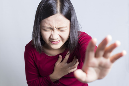 Woman having a pain in the heart area, isolated in white background