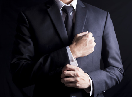 Foto de Businessman Fixing Cufflinks his Suit - Imagen libre de derechos