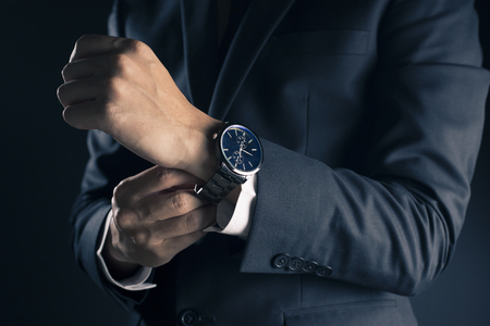Foto per Businessman checking time from watch - Immagine Royalty Free