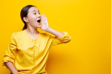 Photo pour Happy woman making shout gesture isolated over yellow - image libre de droit