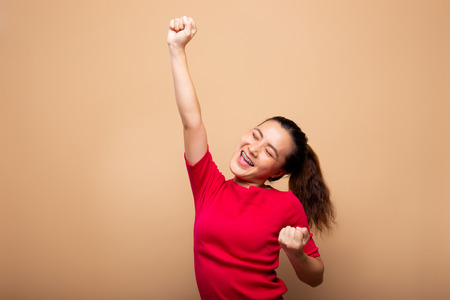 Photo for Happy woman make winning gesture isolated on background - Royalty Free Image