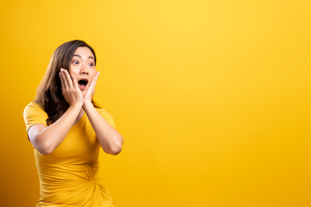 Foto de Portrait of excited woman isolated over yellow background - Imagen libre de derechos
