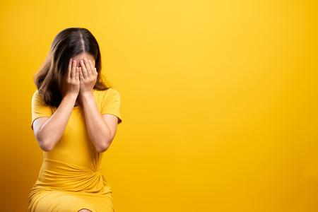 Foto de Sad woman isolated over yellow background - Imagen libre de derechos