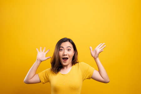 Photo for Happy woman make winning gesture isolated over yellow background - Royalty Free Image