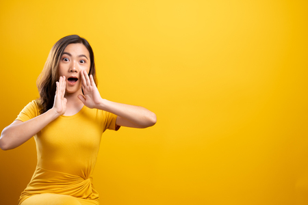 Foto de Woman make gossip gesture isolated over yellow background - Imagen libre de derechos