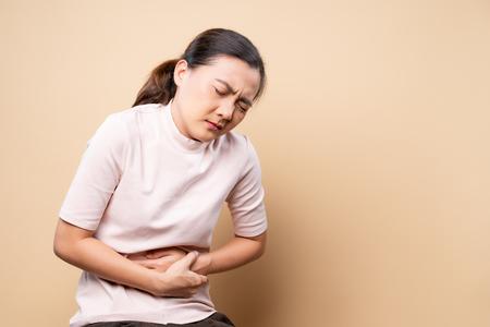 Foto de Woman has stomachache isolated over beige brown - Imagen libre de derechos