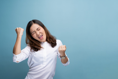 Photo for Happy woman make winning gesture isolated over blue background - Royalty Free Image