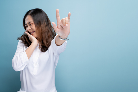 Woman in love showing love sign isolated over blue background