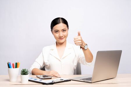 Photo pour Happy woman showing thumb up at office isolated over background - image libre de droit