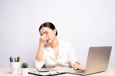 Foto de Woman has eyes pain at office isolated over white background - Imagen libre de derechos