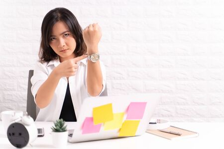 Angry woman pointing at her watch