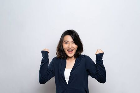 Photo for Portrait of a healthy woman make winning gesture isolated over white background - Royalty Free Image