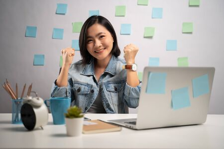 Photo for Asian woman happy make winning gesture working on a laptop at home office. WFH. Work from home. Prevention Coronavirus COVID-19 concept. - Royalty Free Image