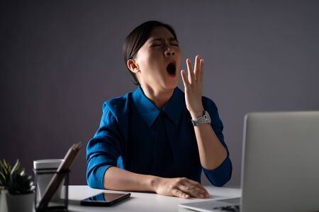 Photo for Asian woman in blue shirt tired and sleepy, yawning at office. isolated on white background. Low key. - Royalty Free Image
