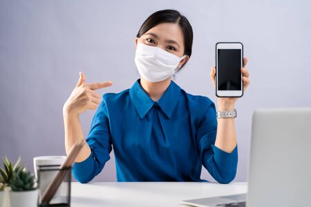 Photo pour Asian woman in blue shirt wearing protective face mask showing blank screen of smart phone and working on a laptop at office. isolated on white background. - image libre de droit