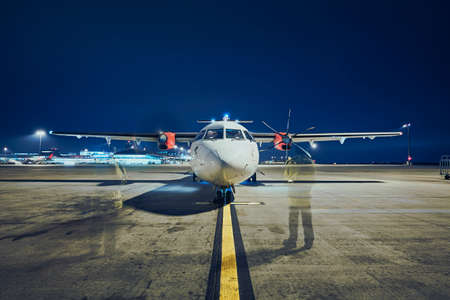 Starting of engines of turboprop airplane before take off against airport at night (long exposure).