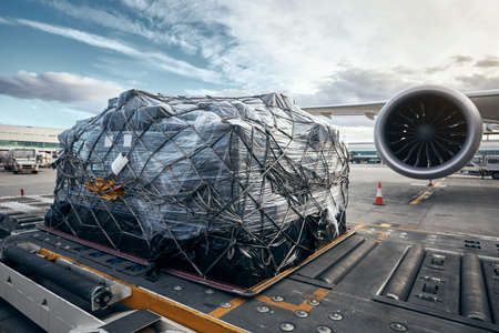 Photo for Preparation before flight. Loading of cargo container against airplane. - Royalty Free Image