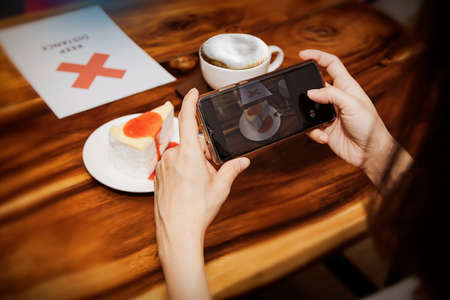 Photo for Women like to take pictures of food and snacks before eating in restaurants : Close-up of a female customer hand using a smartphone to take a photo of the cake on the wooden table as a souvenir. - Royalty Free Image