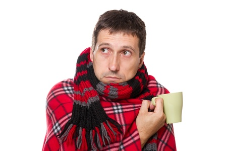 colds man wrapped in a warm blanket and scarf, holding a mug