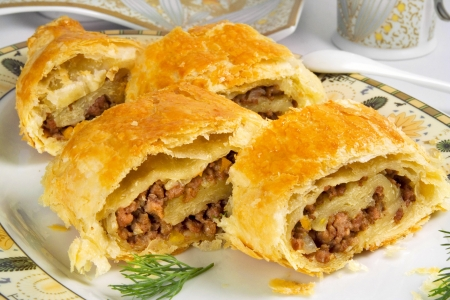 pie with ground beef filling, rolls of  puff pastry with meat on plate