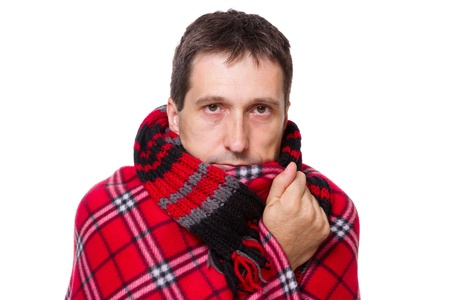 man wrapped in a warm blanket and scarf  shivering from the cold on white background