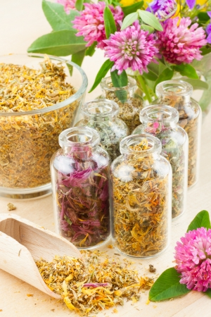 different healing herbs in glass bottles, flowers bouqet, herbal medicine