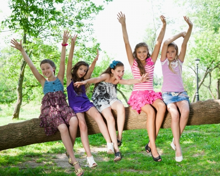 beautiful happy girls sitting on a tree trunk in park