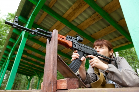 Young woman aiming at a target and shooting an automatic rifle for strikeball  Focus on the rifle