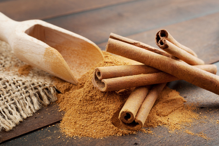 Cinnamon sticks and cinnamon powder in wooden scoop, on table