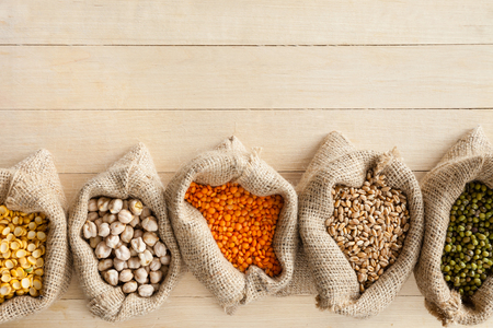hessian bags with cereal grains: peas, chick peas, red lentils, wheat and green mung on wooden table