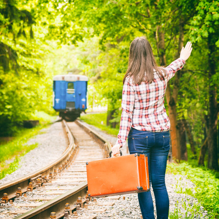 young woman with old suitcase waving his hand, departing train on background