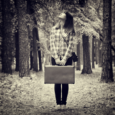 girl with vintage suitcase and camera standing in forest and looking up, retro stylized