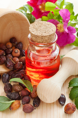 essential oil in glass bottle, dried rose-hip berries and rose hip flowers on table